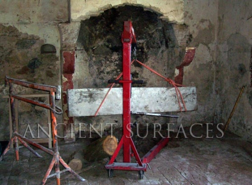 A French Antique fireplace mantel getting reclaimed with the help of a hydraulic crane
