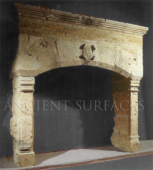 An antique reclaimed Norman era stone fireplace mantel
