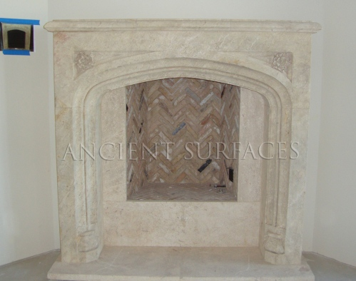 A simple Tudor fireplace hand carved in natural stone installed with herringbone bricks lining the insides of this gas burning firebox.