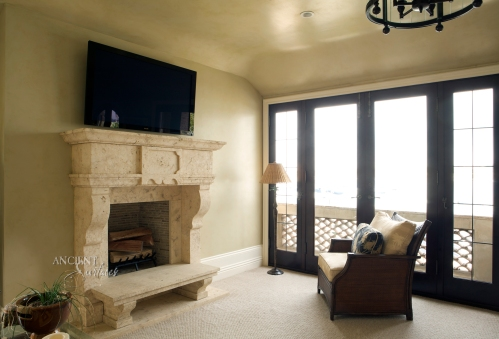Another Italian inspired simple fireplace hand carved in natural stone installed with a benched raised stone hearth.