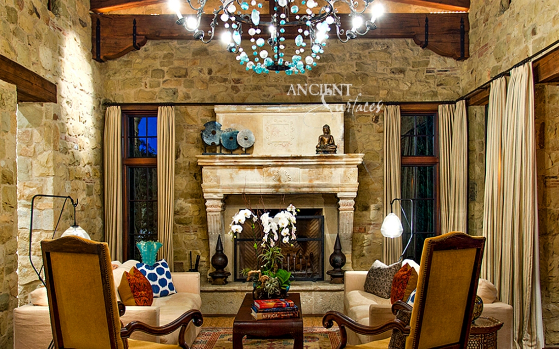 An Antique French limestone fireplace acquired by the current owner of this Mediterranean Countryside style home in Orange Country, California.